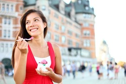 Tourist woman eating ice cream in Quebec City in front of chateau frontenac in Quebec City, Quebec, Canada.