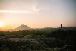 Tourist woman enjoy with beautiful view on mountains, rainforest and valley at sunrise. Traveler woman and Sigiriya Rock (Lion Rock) in background. Dambulla, Sri Lanka