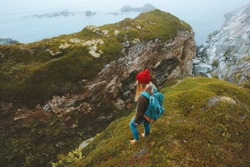 Tourist woman hiking alone with backpack travel vacations adventure lifestyle outdoor explore foggy seaside rocks landscape in Norway