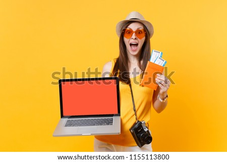 Tourist woman holding laptop pc computer with blank black empty screen passport tickets isolated on yellow orange background. Female traveling abroad to travel on weekends getaway. Air flight concept #1155113800
