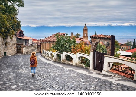 Tourist woman in hat with backpack at the street of Signagi town in Georgia