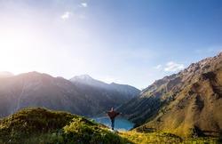 Tourist woman in poncho and rainbow hat enjoying beautiful view of Big Almaty Lake in Kazakhstan