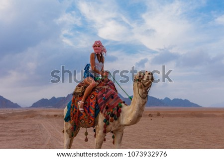 Tourist woman in traditional arabian clothes with camel in the Sinai Desert, Sharm el Sheikh, Sinai Peninsula, Egypt. #1073932976