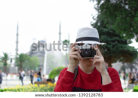 Tourist Woman in white hat with backpack and camera taking photo in front of Blue Mosque in Sultanahmet square Istanbul. Travel guide. Concept of tourism in Europe and Asia. Russian tourists in Turkey