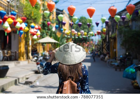 Tourist woman is wearing Non La (Vietnamese tradition hat) and enjoy sightseeing at Heritage village in Hoi An city in Vietnam. #788077351