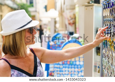Tourist woman looking for the souvenirs in local store on the street summer vacation holiday #1433043323
