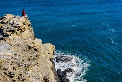 Tourist woman on spanish rocky coastline in Murcia region. Mediterranean Sea coast landscape, Calblanque Regional Park.