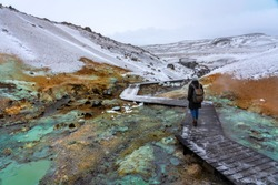 tourist woman on the path of colorful krysuvik seltun on reykjanes peninsula in Iceland