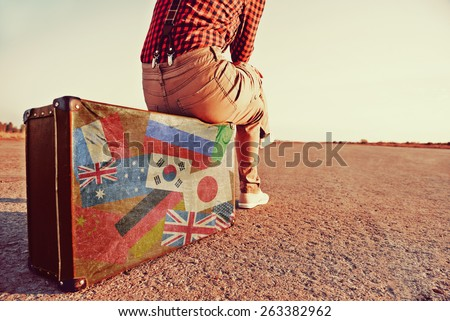 Tourist woman sitting on a suitcase on road. Suitcase with stamps flags of different countries. Concept of travel