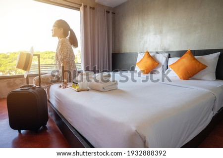 Tourist woman sitting on bed nearly window, looking to beautiful view with her luggage in hotel bedroom after check-in. Conceptual of travel and accommodation.
