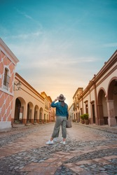 Tourist woman standing in the middle of the street of a magical town, town of La Peña del Bernal in Querétaro, Mexico, with sunset in front, summer day