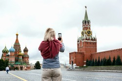 Tourist woman taking photo on her smartphone on Red Square in Moscow, Russia.