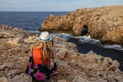 Tourist woman taking picture with her  phone at Cala es Pous bay  in Menorca island at Punta Nati area.