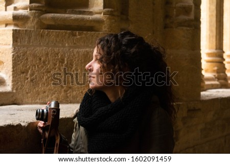 Tourist woman walks through the interior of the cloister of a cathedral with a vintage camera in a Spanish city. Concept: historical tourism, cultural tourism
