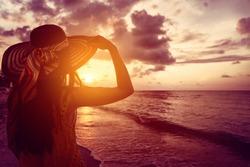 Tourist woman watching sunset at tropical ocean beach