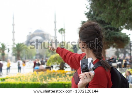 Tourist Woman with backpack and camera taking photo in front of Blue Mosque in Sultanahmet square Istanbul. Travel guide. Concept of tourism in Europe and Asia. Russian tourists in Turkey.