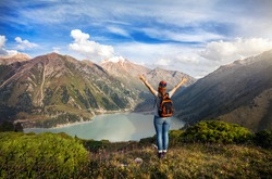 Tourist woman with backpack and rainbow hat rise her hands enjoying beautiful view of Big Almaty Lake in Kazakhstan
