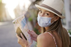 Tourist woman with face mask reading map and using smartphone