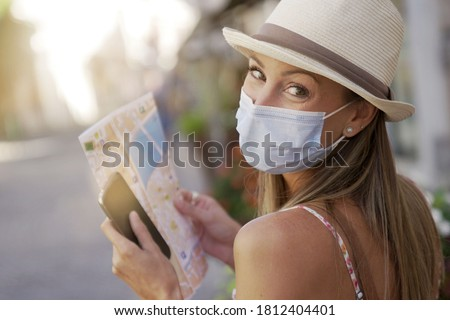 Tourist woman with face mask reading map and using smartphone Foto stock ©