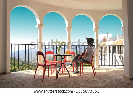 tourist woman with hat, with pants, sitting on the terrace of a bar drinking a beer, with some flowers, next to some arches and the turquoise sky, white village of Frigiliana, Malaga, Andalusia, Spain