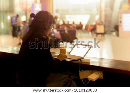 Tourist woman working on laptop with headphone in a coffee shop at the airport #1010120833