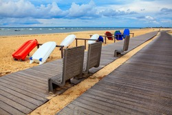 Touristic boats on the sandy beach . Walking path and bench on the seaside