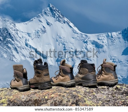 touristic boots on a snowbound rock background