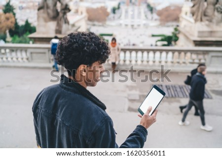 Touristic hipster guy tracking gps via location app on modern digital tablet with copy space area for advertising website for travelers, millennial man chatting via blank touch pad with 4g internet