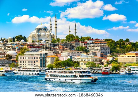 Touristic sightseeing ships in Golden Horn bay of Istanbul and view on Suleymaniye mosque with Sultanahmet district against blue sky and clouds. Istanbul, Turkey during sunny summer day.