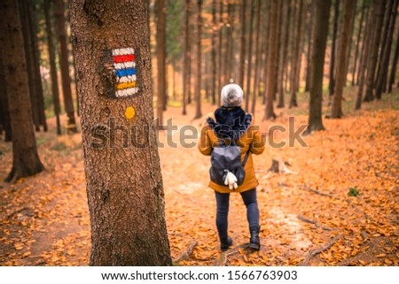 Touristic sign or mark on tree next to touristic path with female tourist in background. Nice autumn scene. Forrest trail. #1566763903