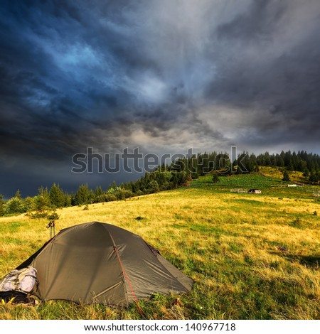 touristic tent and dark storm clouds over hill with pine trees