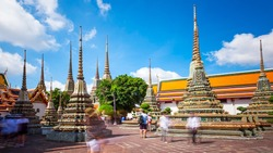 Tourists admire the many buddhist stupas at Wat Pho temple in Bangkok, Thailand (faces blurred for commercial use)