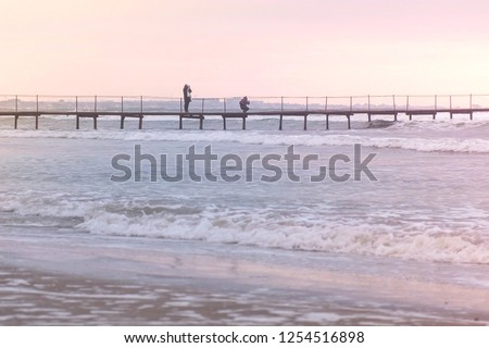 Tourists are photographed on the pier in the sea. Storm on the sea with big waves. Beautiful seascape at sunset. #1254516898