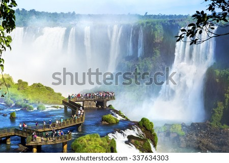 Shutterstock Tourists at Iguazu Falls, one of the world's great natural wonders, on the border of Brazil and Argentina.