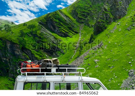 Tourists backpacks and equipment on car trunk in mountains under blue sky - stock photo