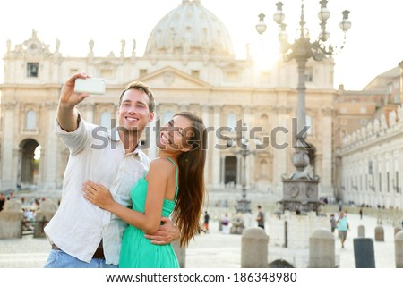 Tourists couple by Vatican city and St. Peter's Basilica church in Rome. Happy travel woman and man taking selfie photo picture on romantic honeymoon in Italy.