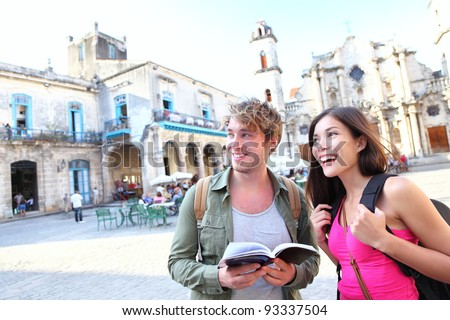 Tourists couple travel in Havana, Cuba having fun. Young multiracial happy couple on backpacking vaction standing on Plaza de la Catedral, Old Havana. - stock photo