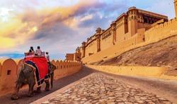 Tourists enjoy an elephant ride at Amer Fort Jaipur Rajasthan at sunset.