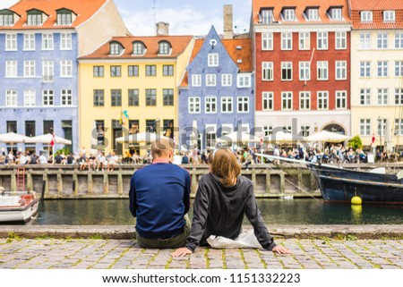 Tourists enjoying the scenic summer view of Nyhavn pier. Colorful building facades with boats and yachts in the Old Town of Copenhagen, Denmark #1151332223
