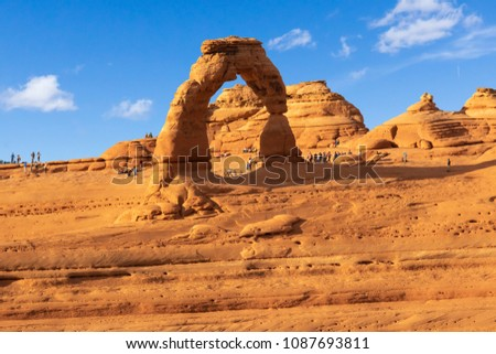Tourists Gather Around Delicate Arch, one of the most popular arches in Arches National Park in Moab, Utah #1087693811
