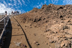 Tourists hike to a viewpoint  on the volcanic cinder of Bartolome island in Galapagos National Park. Different formations of volcanic geology, spatter and tuff cones, lava flows and lava tubes