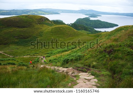 Tourists hiking next to Conic hill in Scotland.