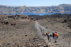 Tourists hiking on the volcanic island Nea Kameni near Santorini in Greece