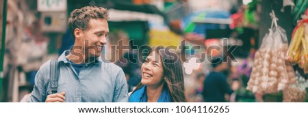 Tourists in Chinatown street market laughing together banner panorama portrait. Asia travel adventure, two people walking visiting Hong Kong. Young woman, man in love.