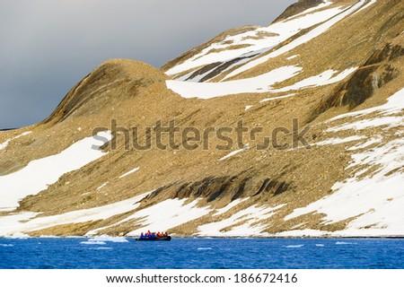 Tourists in inflatable ocean rafts in the Arctic Ocean, Hornsund, Norway.