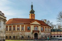 Tourists in Libechov, old abandoned baroque castle in central Bohemia,Czech republic.Romantic building with tower,red facade and park.Rebuilt as Renaissance chateau surrounded by wide water moat