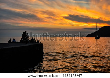 Tourists in silhouette take photos of the sunset and a small boat from the pier at the harbor of Vernazza, Italy