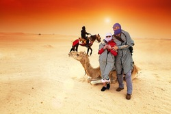 Tourists in the Sahara desert near to camel.In the background is rider on the horse, unrecognizable person.Sunset light, lens flare