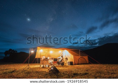 Tourists in yellow tent camping on hill with milky way in the night sky at national park