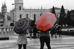 tourists landscape in Belem in black and white with blurred background. orange umbrella focused in contrast to the rest of the photo. contrast between colors